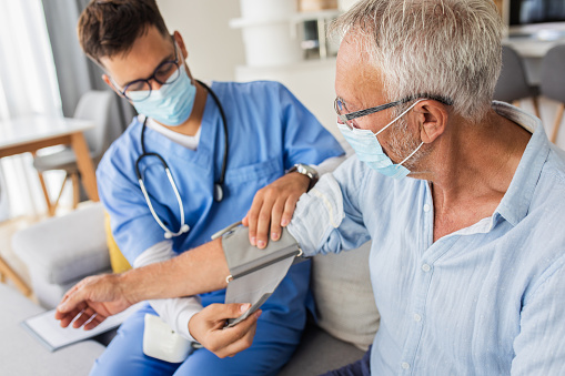 Male nurse measures blood pressure to senior man with mask while being in a home visit.