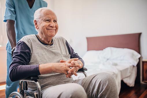 Group of people, male nurse pushing senior paraplegic sitting in wheelchair in nursing home.