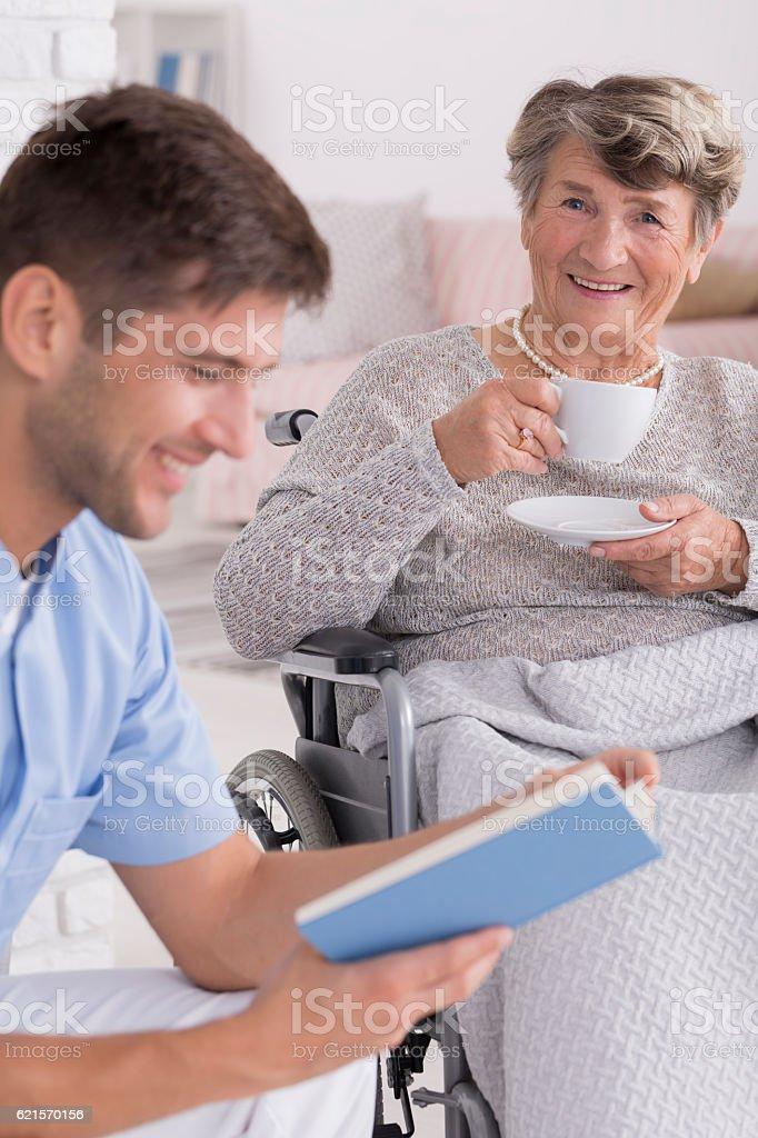 Male nurse reading a book to senior photo libre de droits
