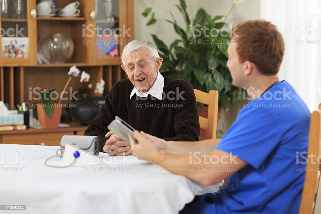 Male Nurse Visiting Senior Patient at Home royalty-free stock photo