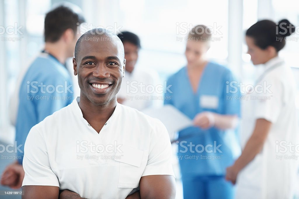 Male nurse with medical team in the background royalty-free stock photo
