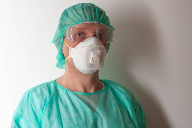 Male nurse, with plastic protective eyeglasses and respirator ffp1, cap, gown, gloves,  with  personal protective equipment to protect against the virus covid-19 in ICU in hospital. stock photo