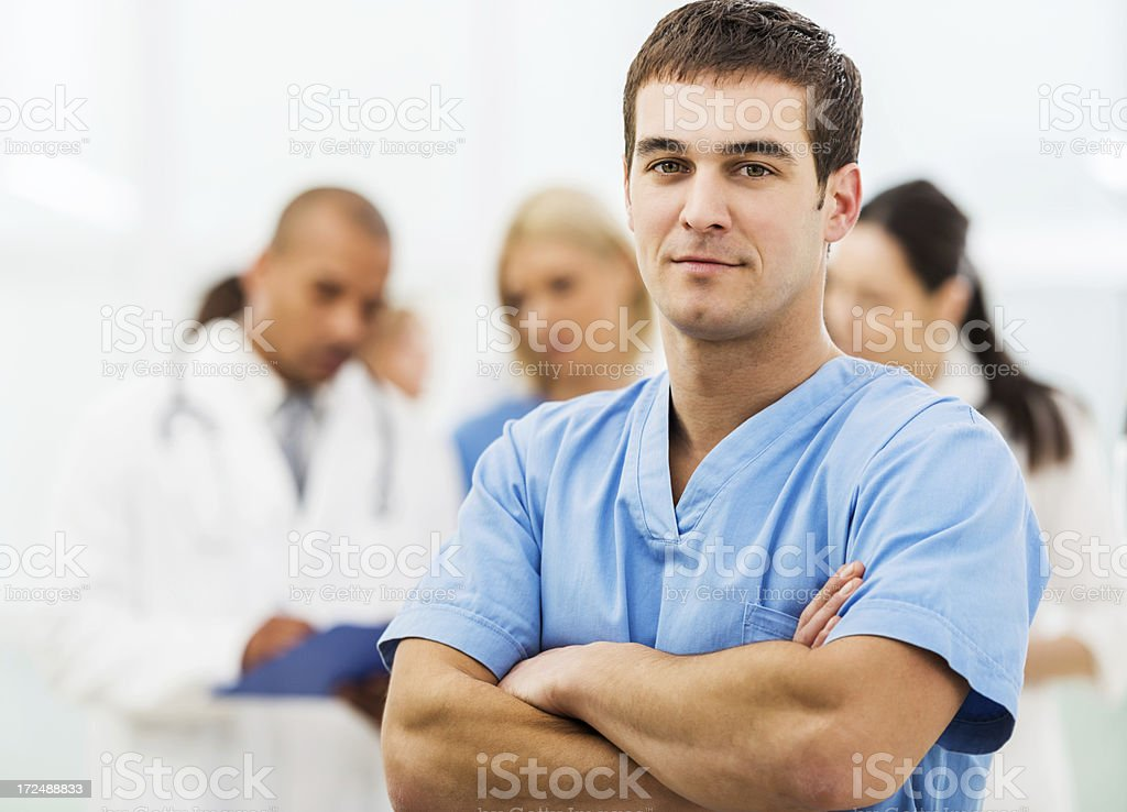 Male nurse with team of doctors in the background. stock photo