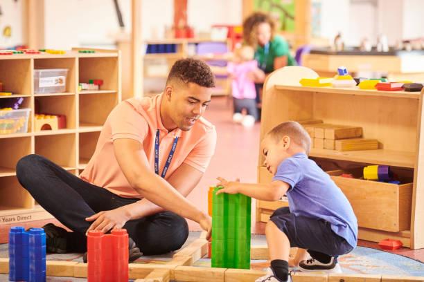 male nursery teacher maths through play in a day nursery preschool teacher stock pictures, royalty-free photos & images