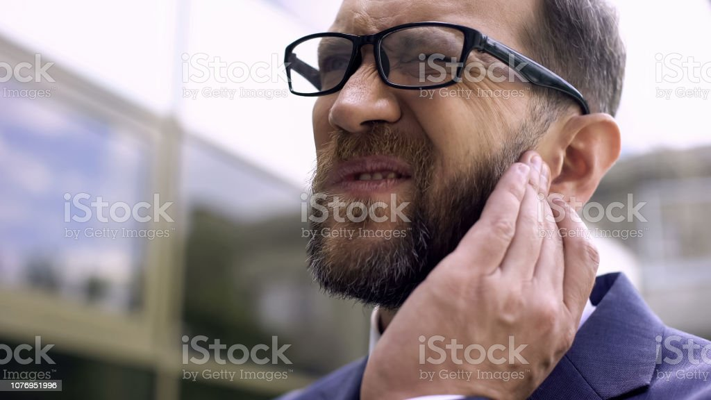 Male of business has ear pain, bacterial infection, inflammation,...