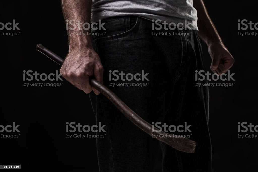 Male offender with a scrap. On black background at the studio stock photo