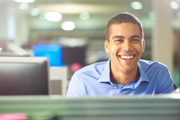 male office worker chatting to colleague stock photo