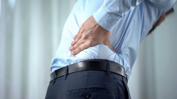 male office worker feeling sharp back pain, sedentary lifestyle, slipped disc - ernia foto e immagini stock