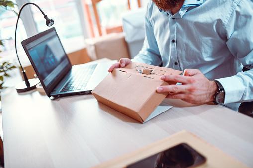Male Office Worker Folding A Cardboard Package