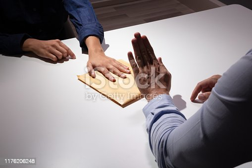 Close-up Of A Businessman's Hand Refusing To Take Bribe From Businesswoman Over The White Desk