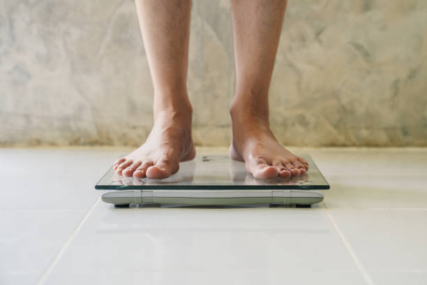 Male on weight scale on floor background, Diet concept. Male on weight scale on floor background, Diet concept. anorexia nervosa stock pictures, royalty-free photos & images