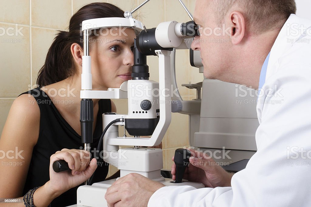 Male ophthalmologist performing an eye examination - Royalty-free Adult Stock Photo