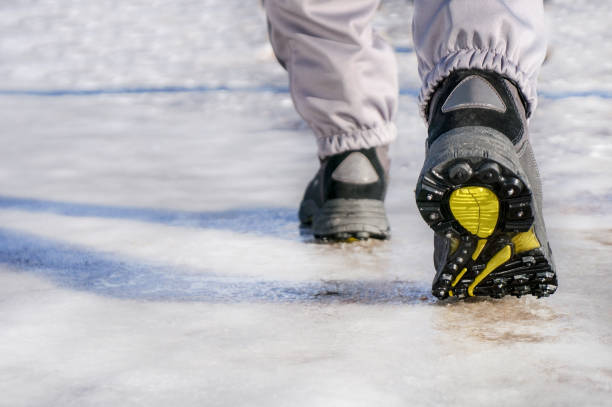 male or female winter boots walking on snowy sleet road male or female winter boots walking on snowy sleet road with spikes on sole studded stock pictures, royalty-free photos & images