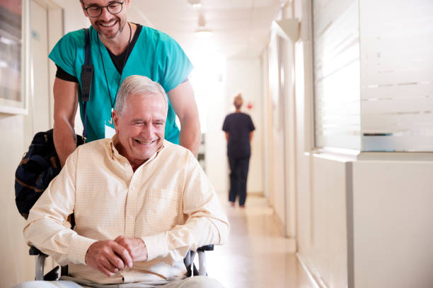 male orderly pushing senior male patient being discharged from hospital in wheelchair - leaving stock photos and pictures