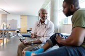Serious male orthopedic doctor uses a digital tablet to show an injured male patient a video about appropriate exercises to strengthen the patient's food and ankle. The patient's food and ankle are wrapped with kinesiology tape.