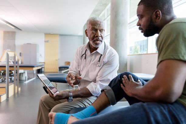 o doutor ortopédico masculino mostra exercícios ao paciente na tabuleta digital - ortopedia - fotografias e filmes do acervo