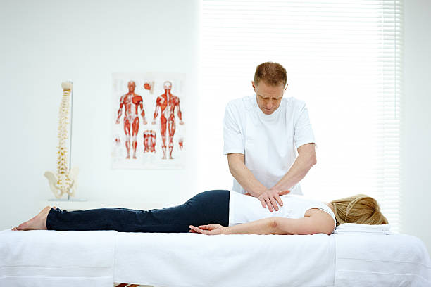 male osteopath treating back problem of a woman - chiropractic care stock photos and pictures