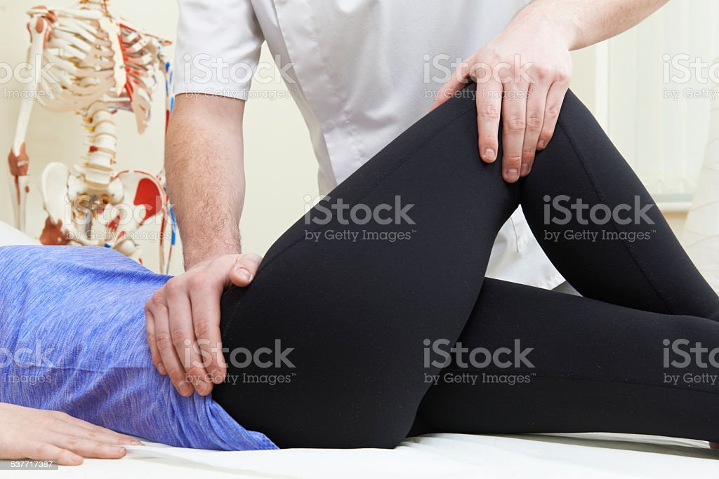 Male Osteopath Treating Female Patient With Hip Problem stock photo