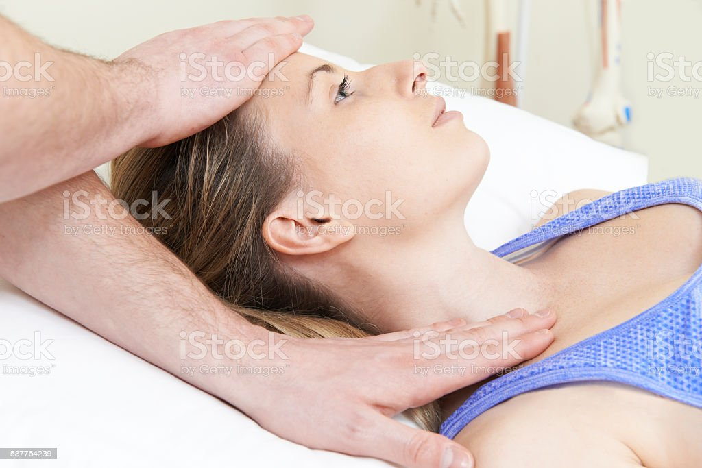 Male Osteopath Treating Female Patient With Neck Problem stock photo