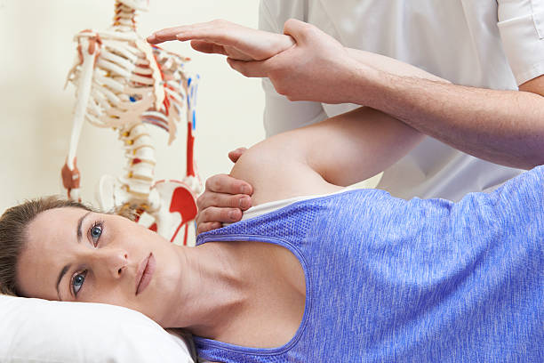 male osteopath treating female patient with shoulder problem - shoulder surgery stock photos and pictures
