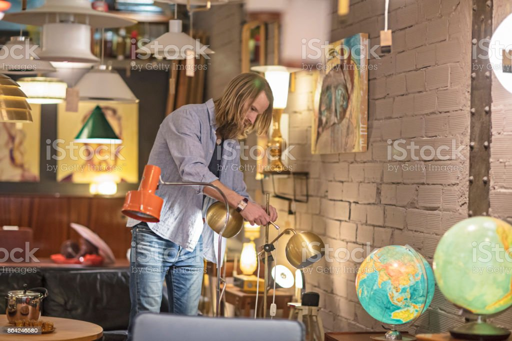 Male owner adjusting desk lamp in furniture store royalty-free stock photo