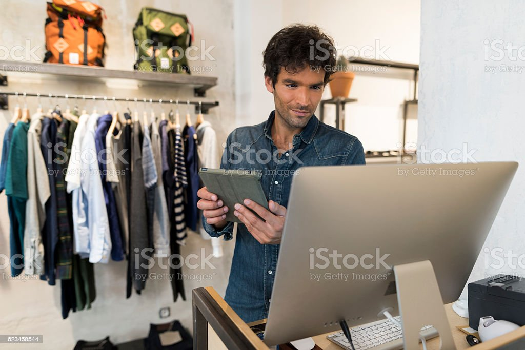 Male owner of Fashion Store with digital tablet and computer bildbanksfoto