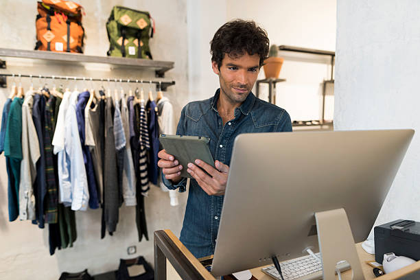Male owner of Fashion Store with digital tablet and computer stock photo