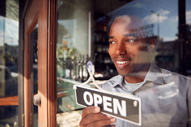 Male Owner Of Start Up Coffee Shop Or Restaurant Turning Round Open Sign On Door stock photo