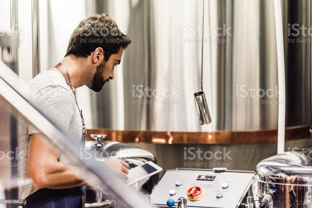 Male owner with tablet working at microbrewery stock photo