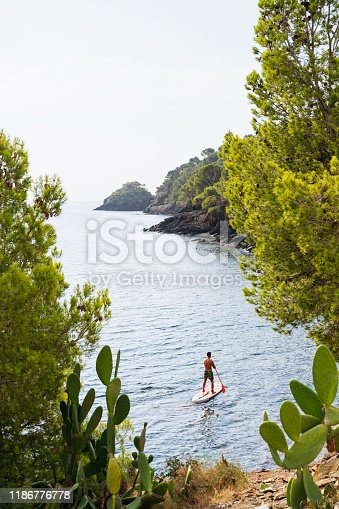 High angle view of Spanish middle-aged male paddleboarder floating along Costa Brava shoreline in early morning.