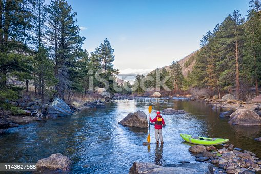 male paddler with an inflatable whitewater kayak - Poudre River below Mishiwaka, Colorado in early spring