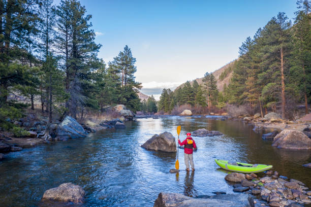 male paddler with an inflatable whitewater kayak stock photo