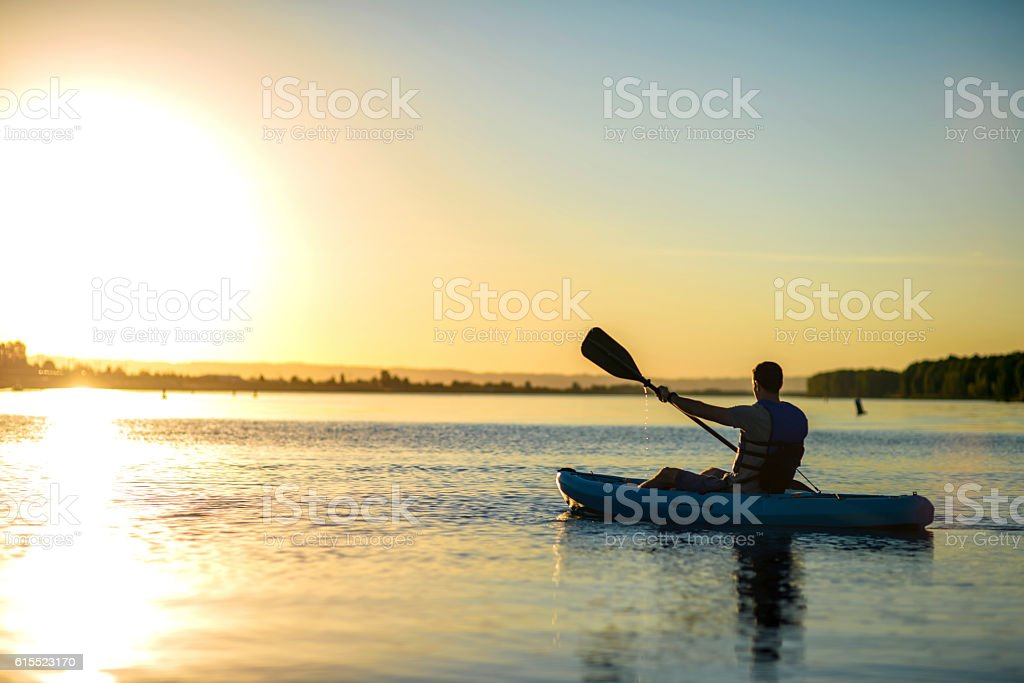 Male paddling a kayak on water as the sun sets - Photo