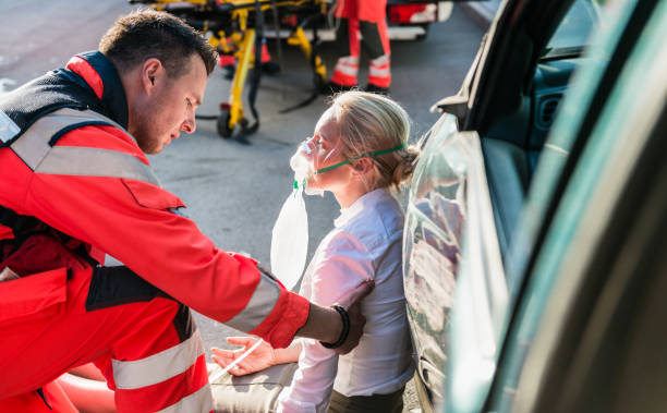 male paramedic helping injured woman - paramedic stock pictures, royalty-free photos & images