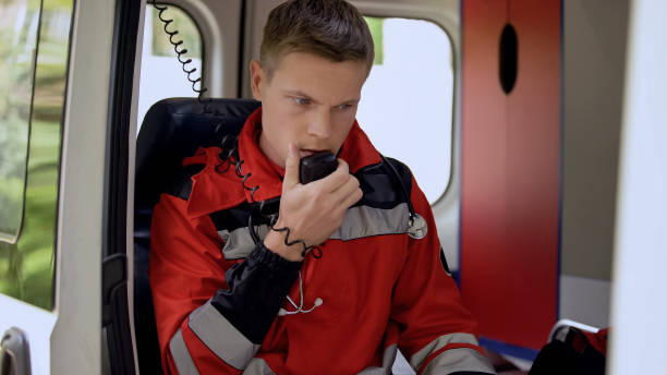 Male paramedic talking by radio, sitting in ambulance, ready to drive on call stock photo