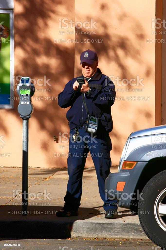 A Male Parking Enforcement Officer Digitally Writes A Ticket