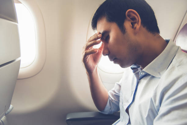 Male passenger having airsickness on the plane Male passenger feeling dizzy having airsickness while traveling on the plane jet lag stock pictures, royalty-free photos & images