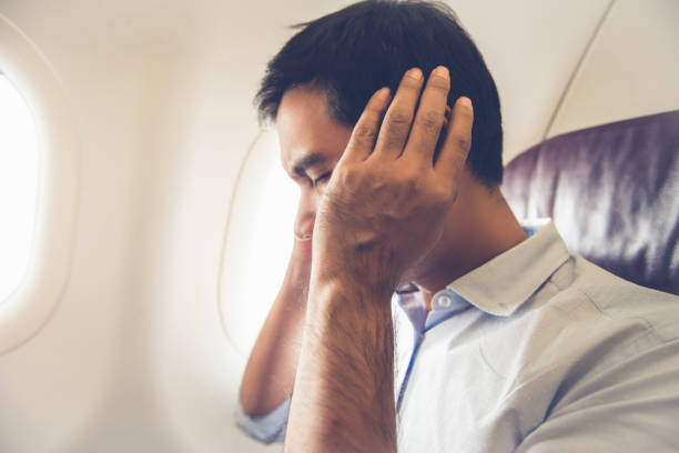 Male passenger having ear pop on the airplane Male passenger having ear pop on the airplane while taking off (or landing) hands covering ears stock pictures, royalty-free photos & images