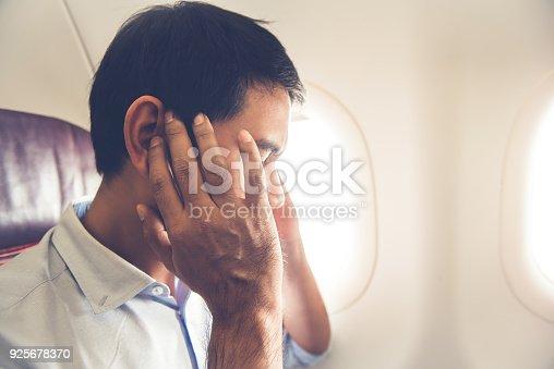 istock Male passenger having ear pop on the airplane 925678370