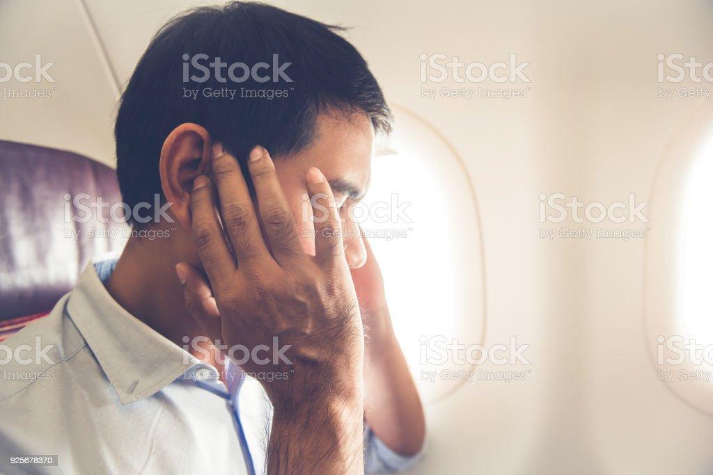 Male passenger having ear pop on the airplane stock photo