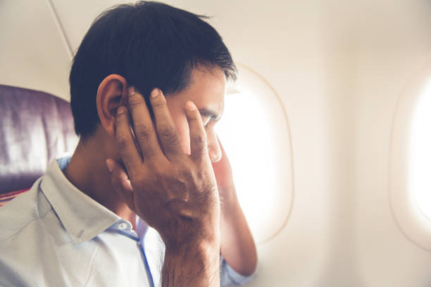 male passenger having ear pop on the airplane - ear stock photos and pictures