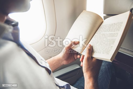 istock Male passenger killing time by reading book while traveling on the airplane 922392468