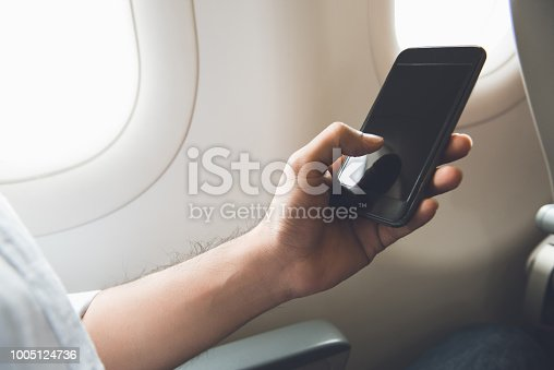 istock Male passenger turning off mobile phone on the airplane 1005124736