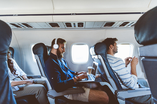 Young bearded man sitting inside an airplane and using a laptop. Male passenger using computer during flight.