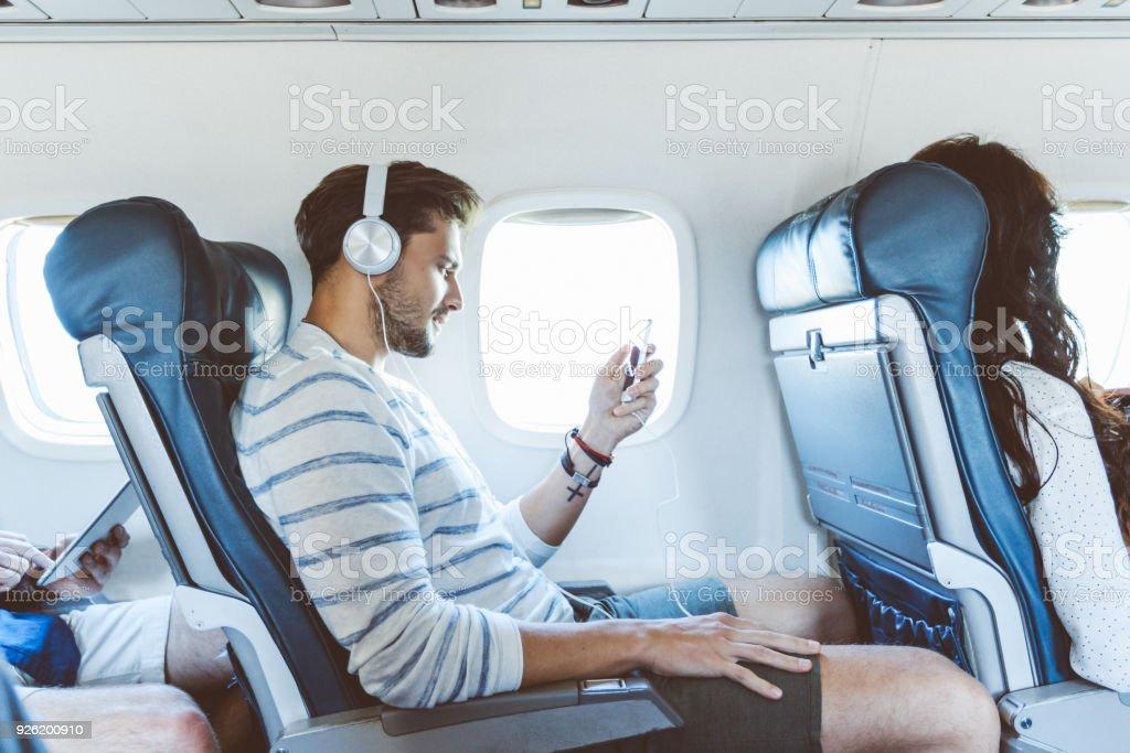 Male passenger using mobile phone during flight stock photo