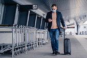 Male passenger walks in airport, holds suitcase, checks newsfeed on smartphone, wears disposable medical mask during pandemic coronavirus, tries to be safe during disease virus. Respiratory symptoms