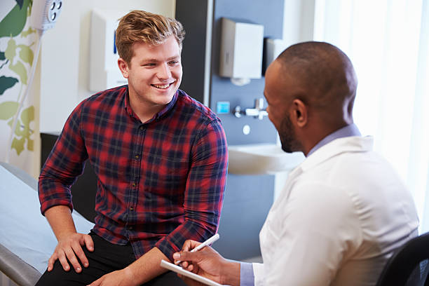 Male Patient And Doctor Have Consultation In Hospital Room stock photo