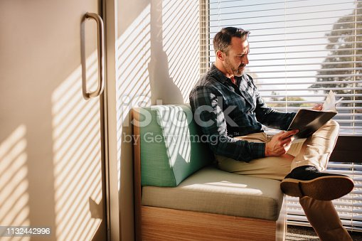 Mature male patient reading a book in the doctor's waiting room. Male patient at reception of clinic, sitting on sofa with a book.