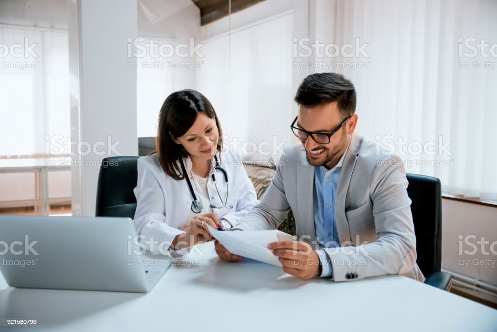 Male patient consulting doctor in clinic stock photo