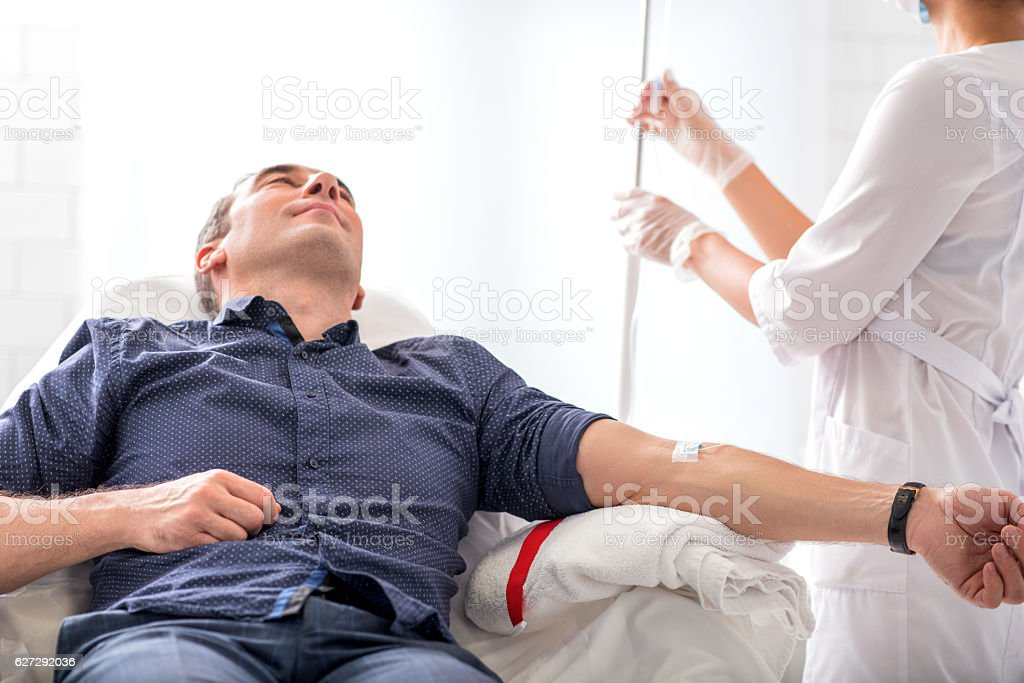 Male patient getting intravenous procedure in hospital stock photo
